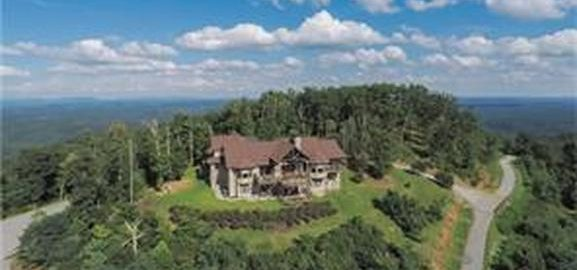 aerial view of home exterior, surrounded by mountain and trees.
