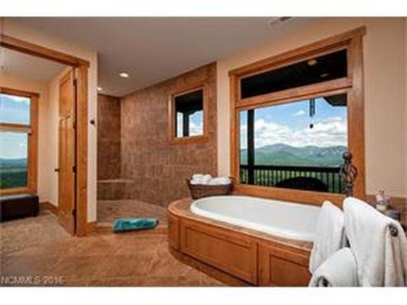 large master bath with jetted pool and large open shower to left.