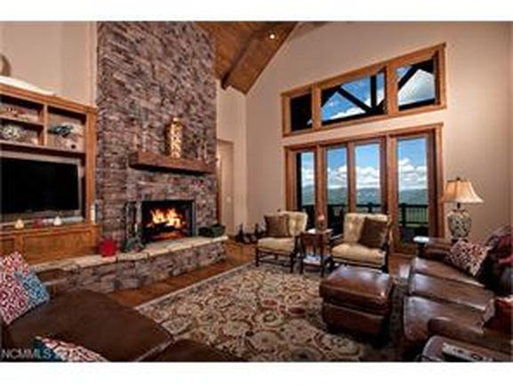 stone fireplace and cozy surrounding living room furniture, wood accent to windows.