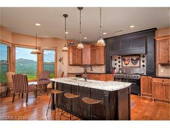 open kitchen with large window on the left with views of mountain, large granite countertop and double oven.