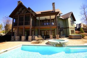 Front of vacation home with in-ground pool and balcony.