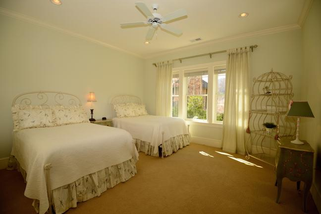 Large light-filled bedroom with two double beds and silk drapes.
