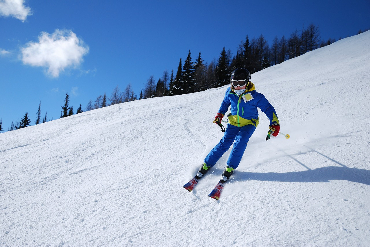 Man in a blue jacket skiing.