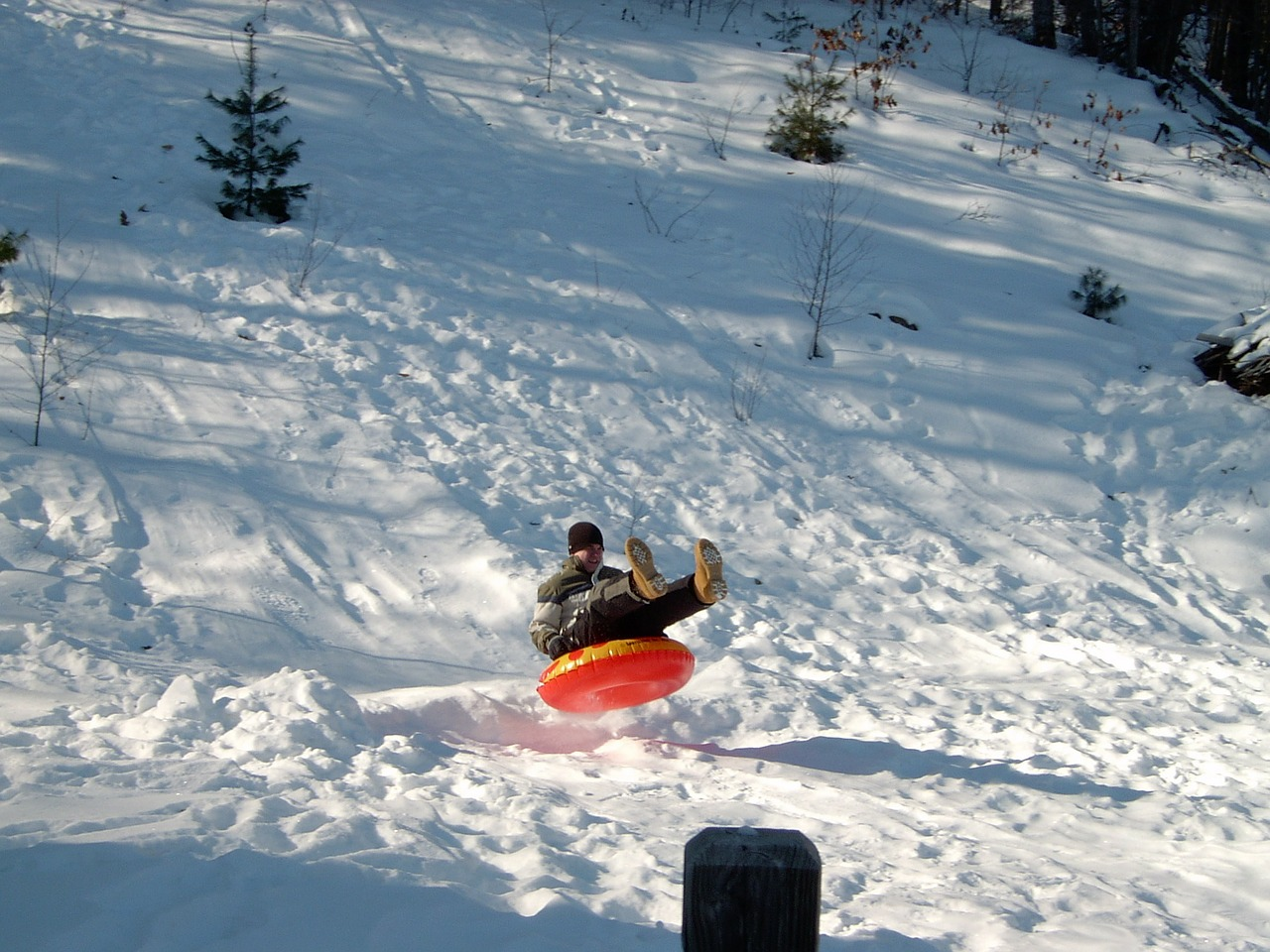 Man in a red inner tube going down the mountain.
