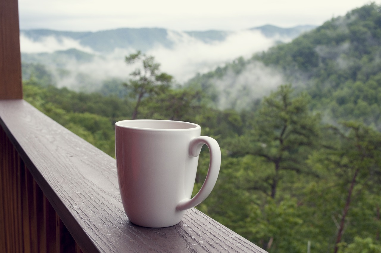 Cup of coffee on a ledge overlooking the mountains.