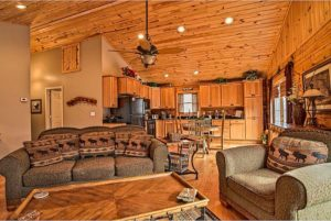 Wood paneled interior with a huge couch, large kitchen, and game table.