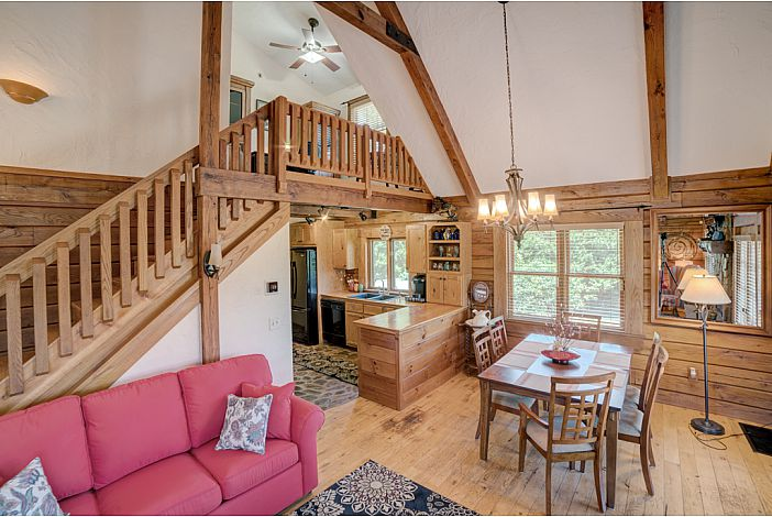 Spacious log cabin interior with lofted stairs.