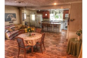 Wood paneled kitchen floor with large table, open floor plan, and top-of-the-line appliances.