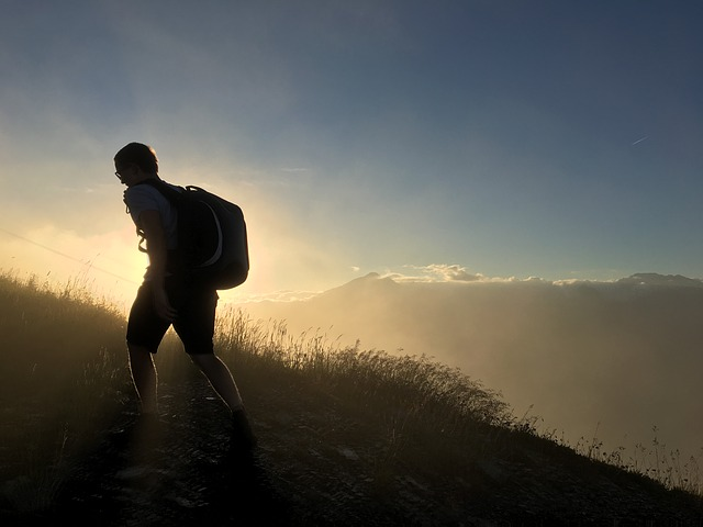 Silhouette of an adult walking up a mountain.