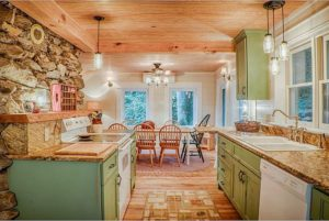 Spacious kitchen with green cabinets.