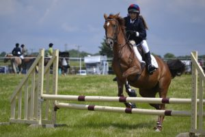 Woman on a horse completing a jump at an equestrian event.
