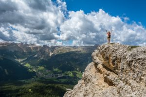 A hiker celebrates reaching the top of a treacherous looking mountain hiking trail