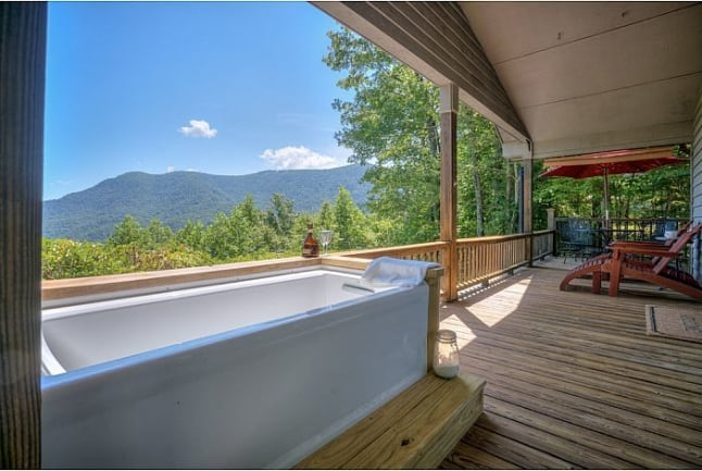 Bathtub sitting on the back deck with a mountain view.
