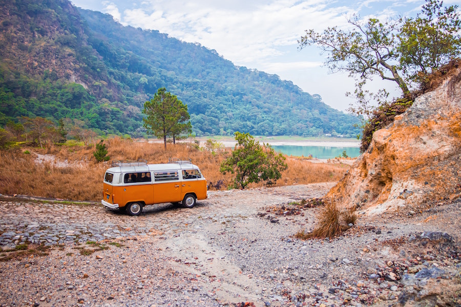 A van on the shore of a lake.