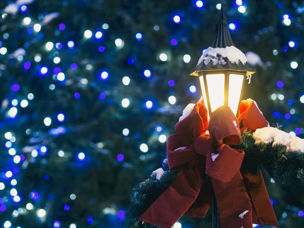 A lamp decorated with a red bow surrounded by Christmas lights for one of the holiday events.