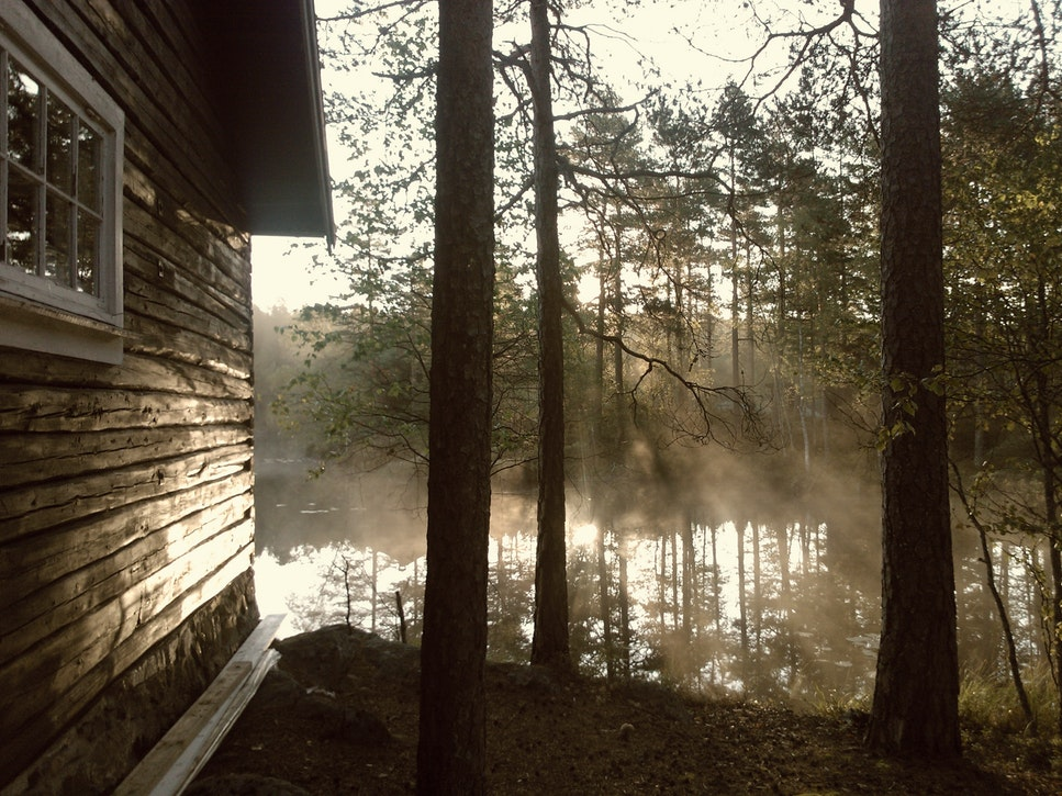 A cabin by a body of water that you'll find when Buying a Home in Western NC.
