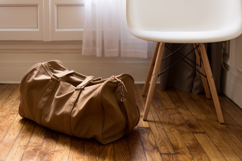 A duffel bag sitting on the floor by a chair.